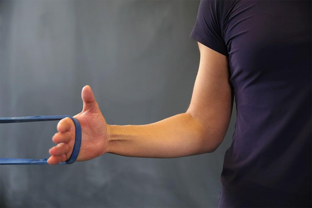 Frau macht Innen- und Außenrotation mit Fitnessband