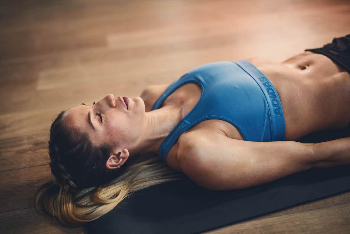 Una mujer está tumbada sobre la esterilla de yoga con los ojos cerrados