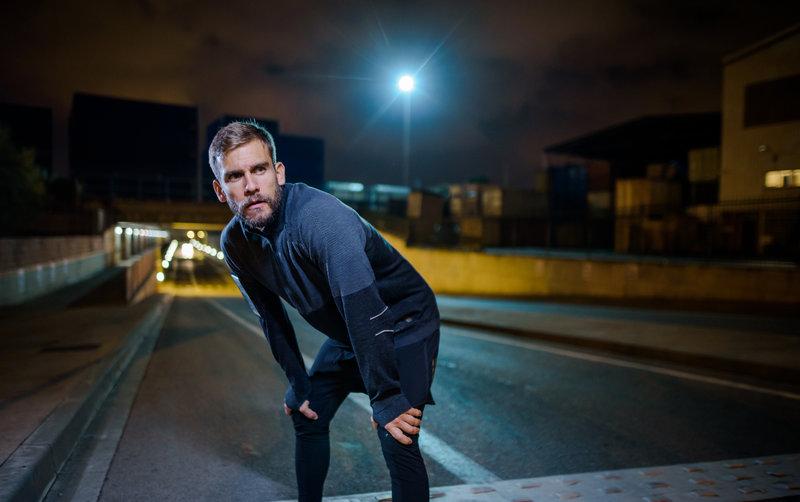 Ein Mann braucht während dem Laufen eine Verschnaufpause