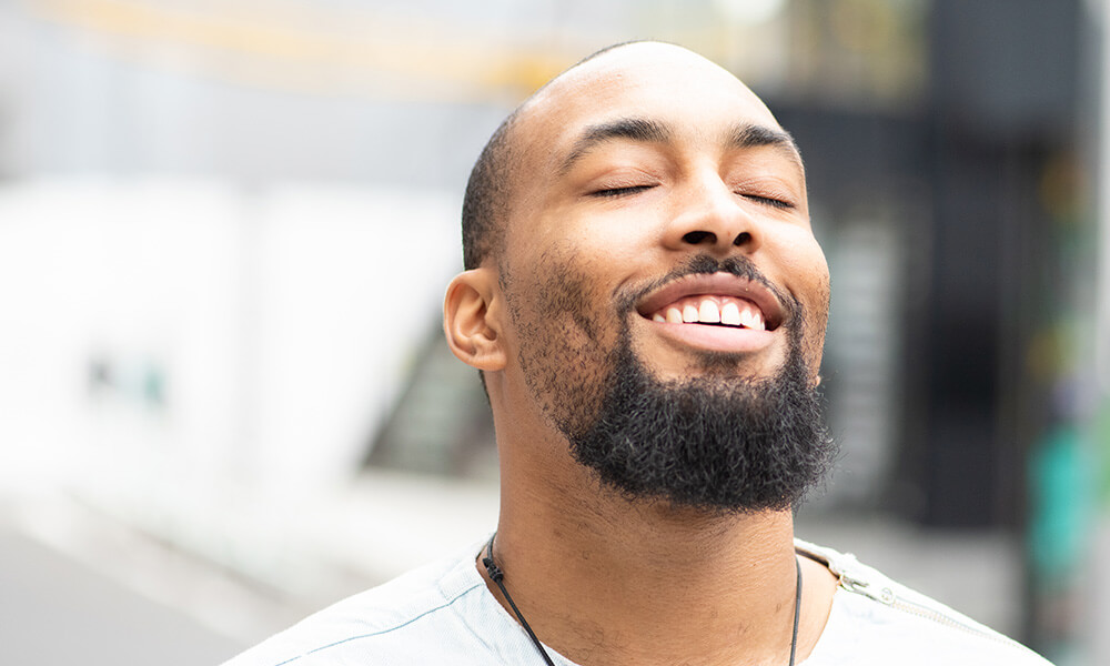 Ein Mann lacht und hält sein Gesicht in die Sonne