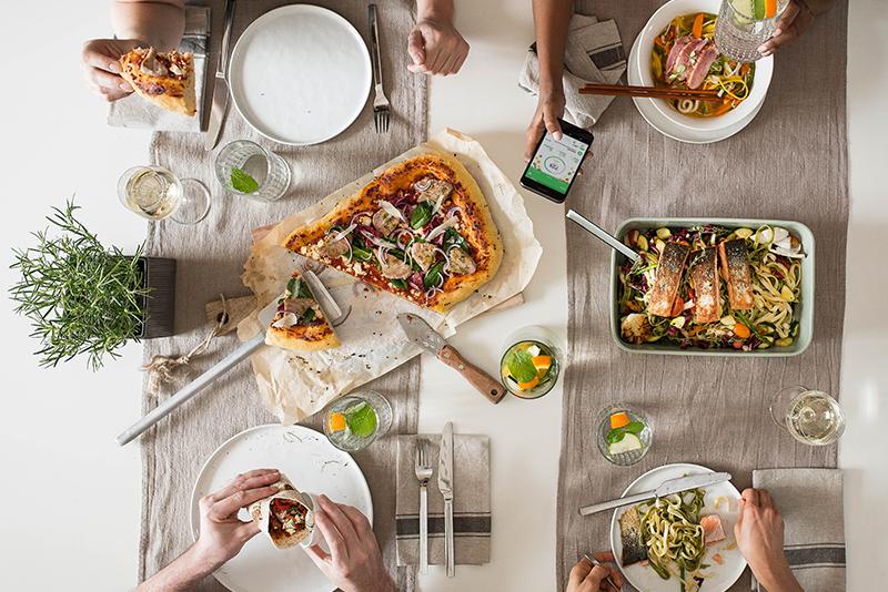 Vier Menschen sitzen am Tisch, essen Mittag und tracken es mit der Runtastic Balance App
