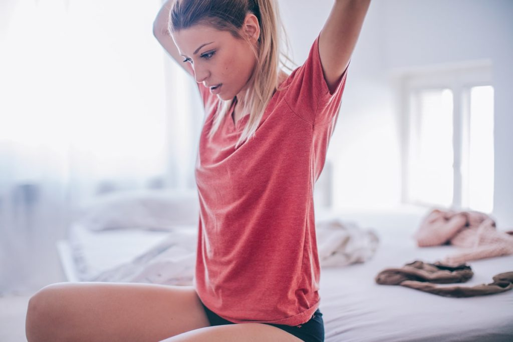 Woman waking up on her bed