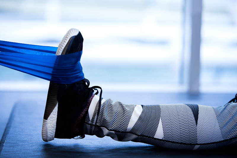 A close-up of a woman stretching her foot with a resistance band
