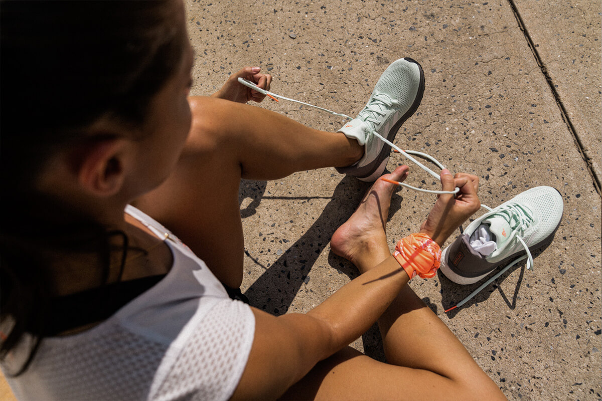 mujer calzándose zapatillas de running