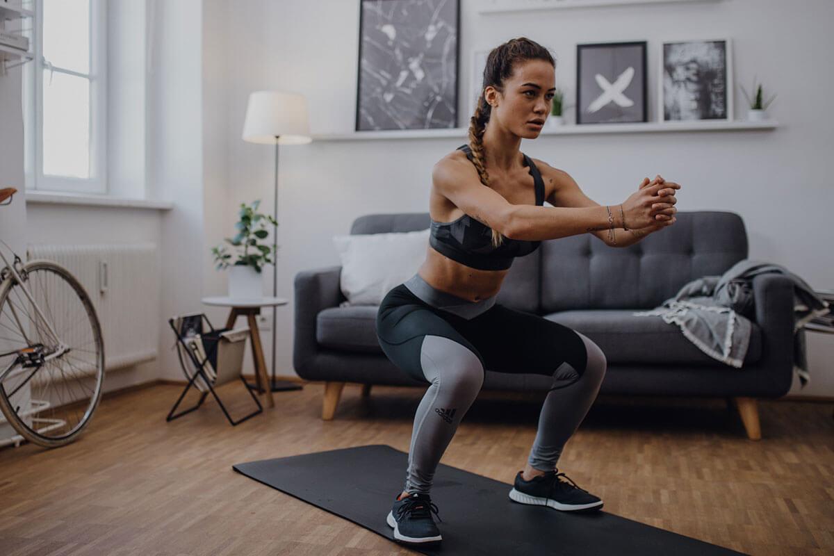 Une femme fait des squat chez elle