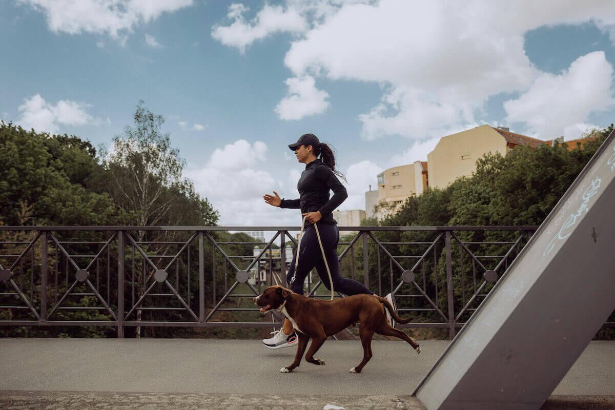 Une femme court avec son chien