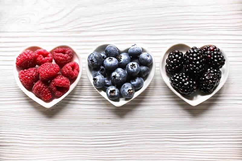 Raspberries, blueberries and blackberreis on heart shaped plates.