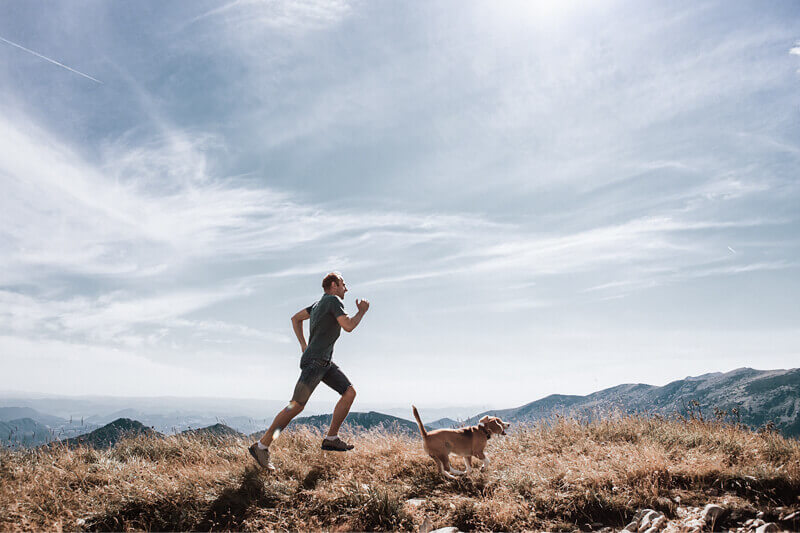 A young man running with his dog in the mountains