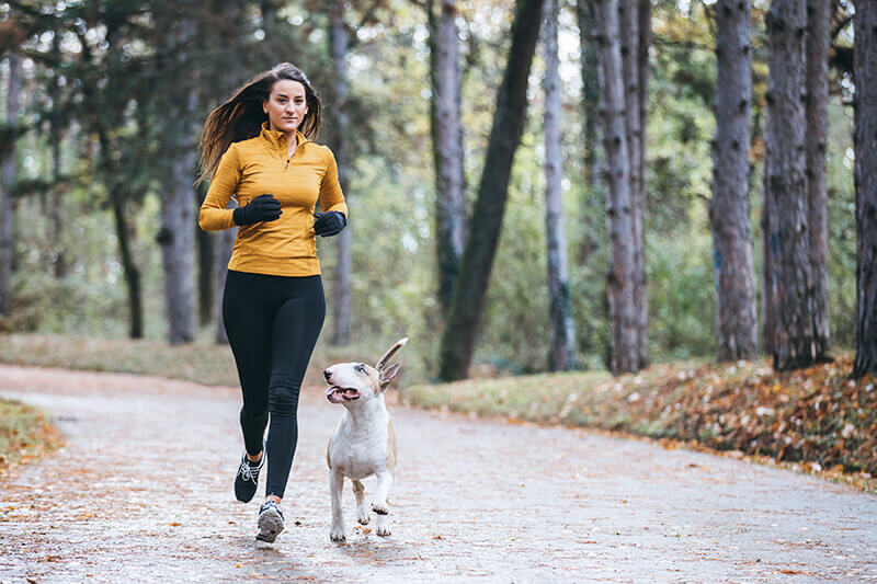 A young lady runs with her dog in the woods