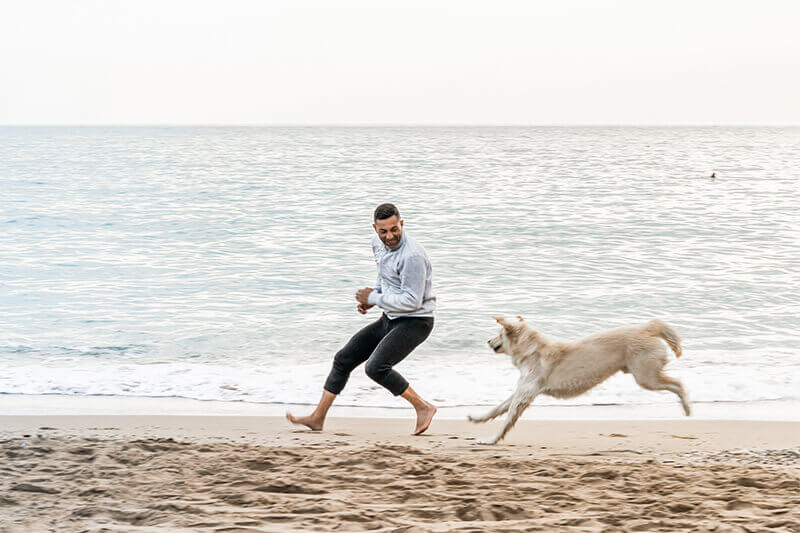 A young man with his dog on the beach