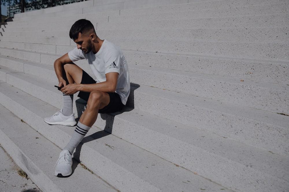 Homem sentado em uma escadaria na rua mexendo no celular