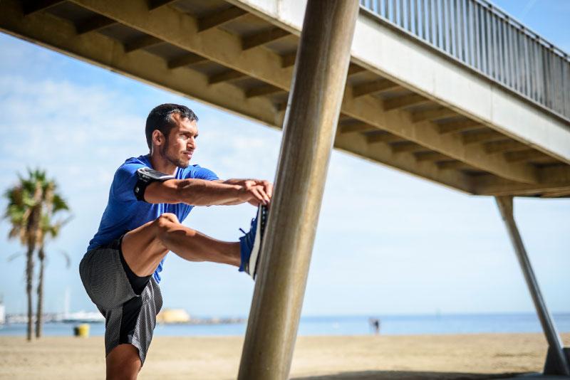 Mann dehnt sich nach dem Joggen am Strand