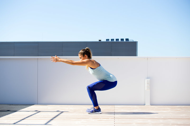 Woman is doing a squat with arms falling forward