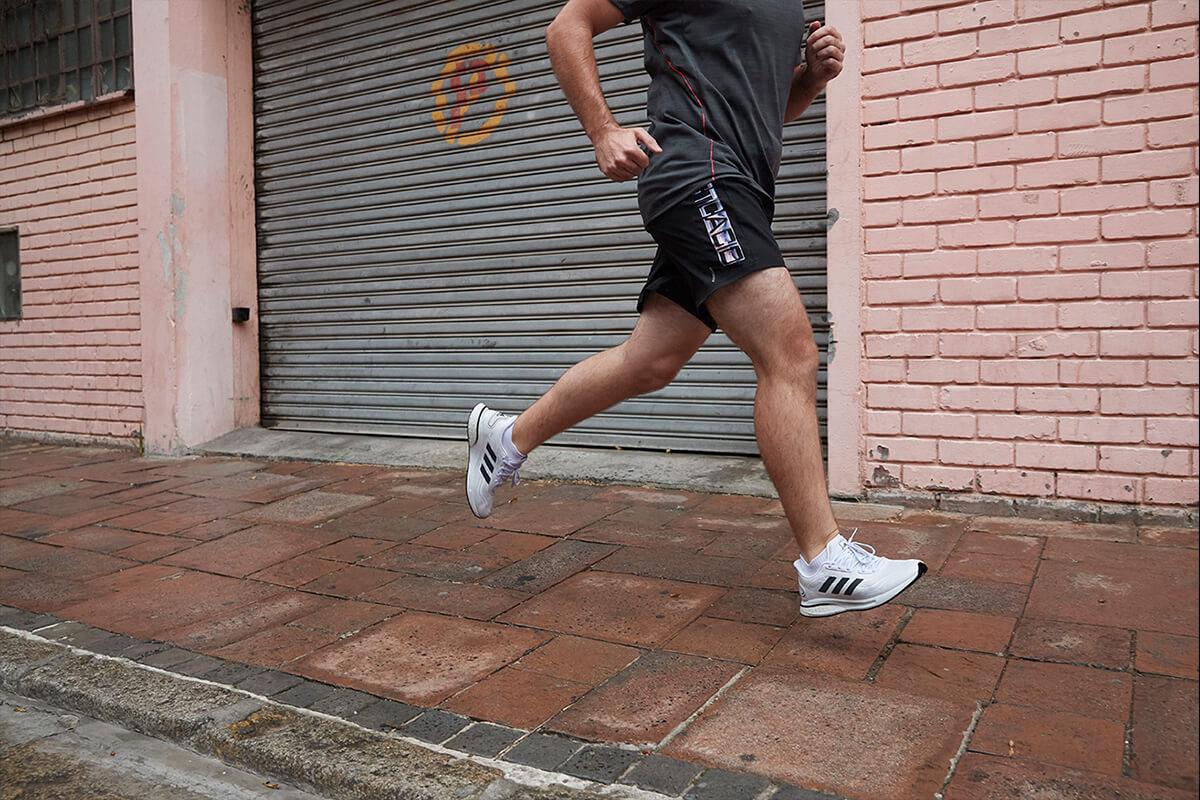 Homem correndo na calçada