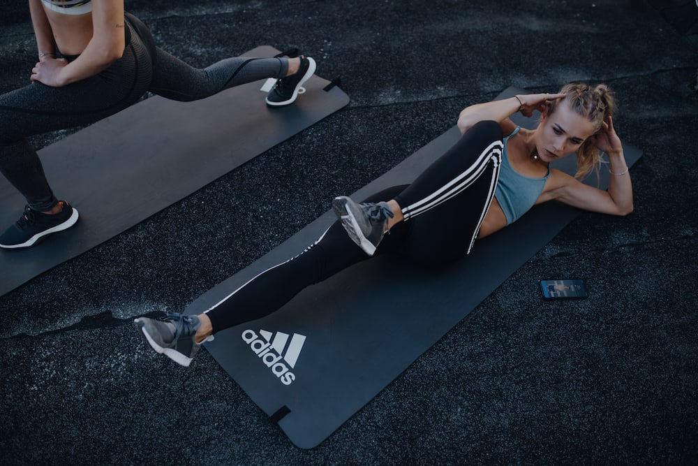 28-day workout challenge for beginners: A young woman is doing bicycle crunches