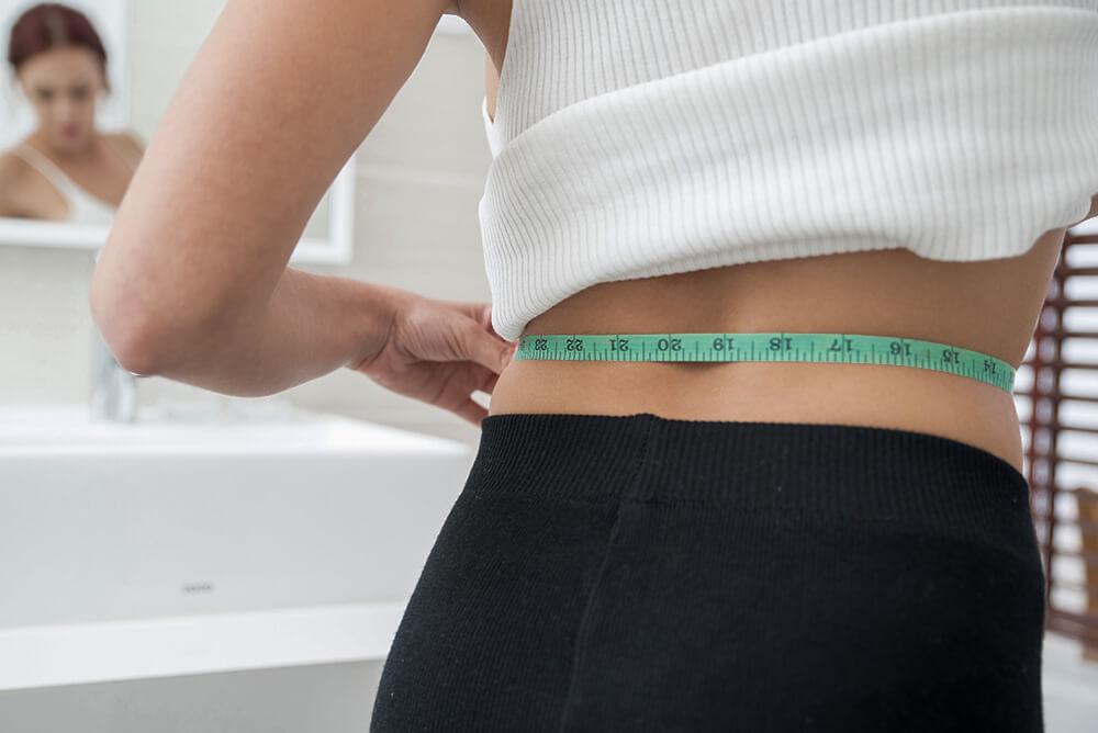 Mulher medindo a cintura
