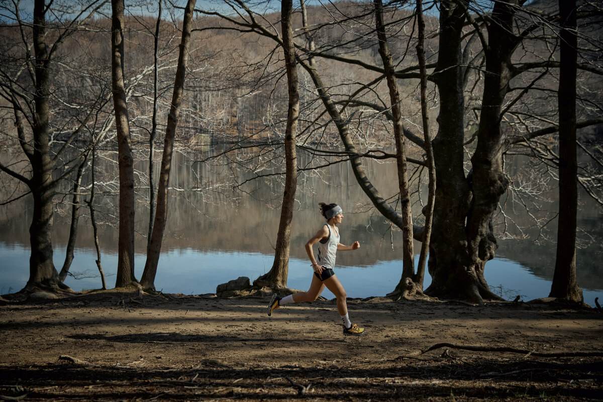 A woman is trail running in the woods