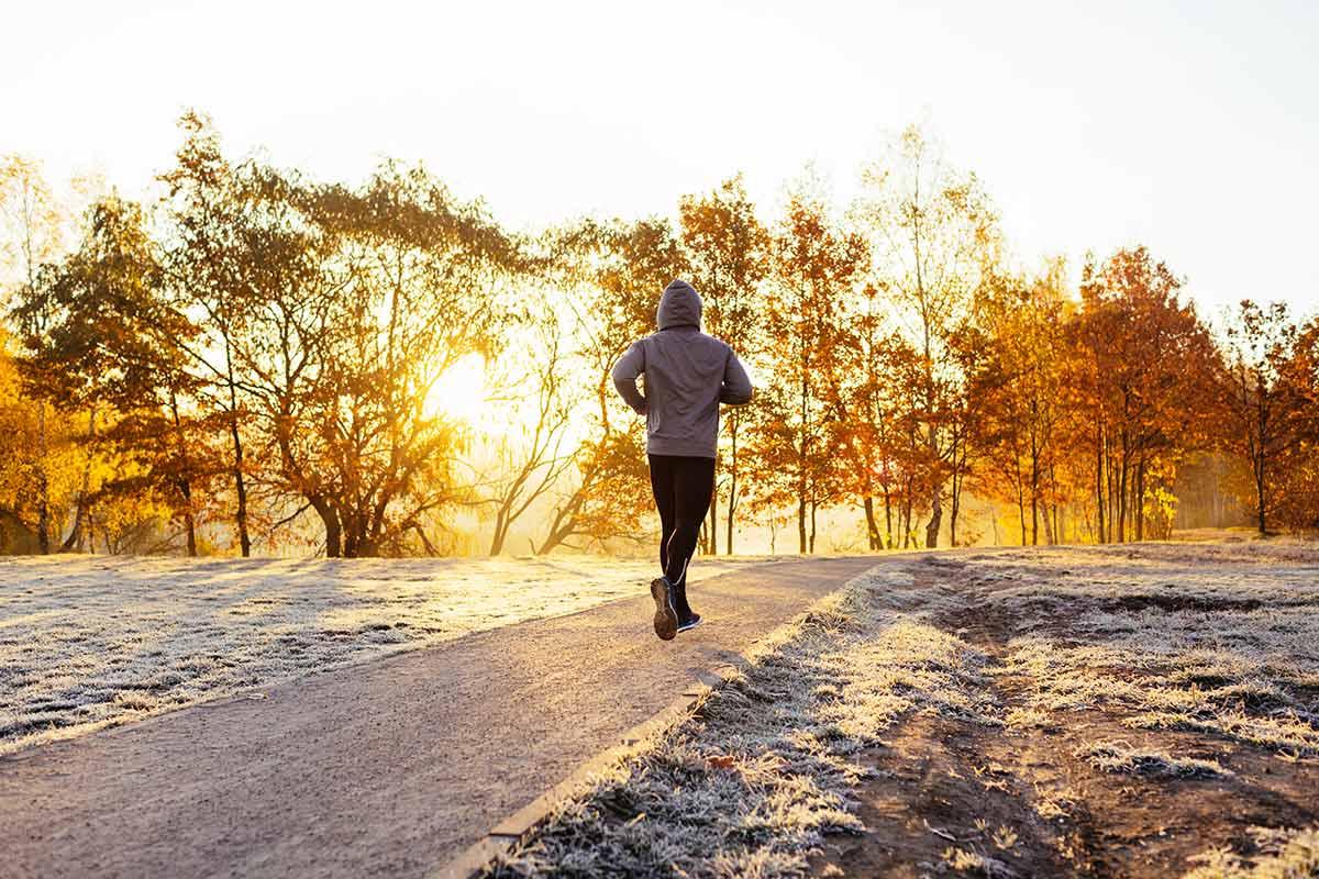 Homem correndo no chão com neve e um lindo nascer do sol ao fundo.