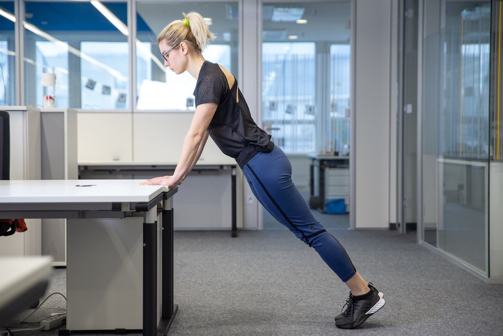 Woman doing push up on a desk