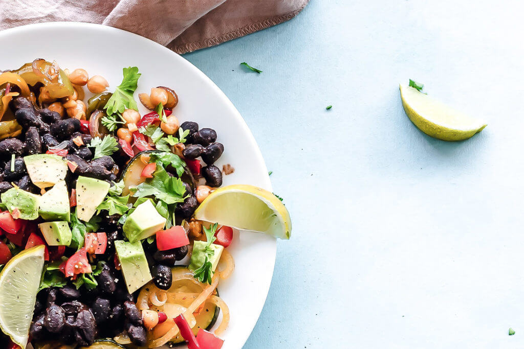Ingredients for a vegan diet meal: avocado, tomato, black beans, chickpeas