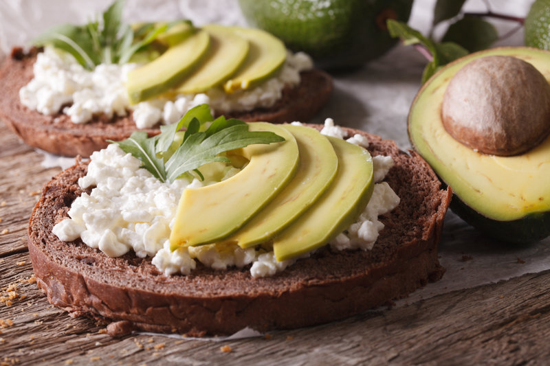 Healthy snack for Nighttime weight loss: sandwiches with avocado, cream cheese and arugula close-up on the table.