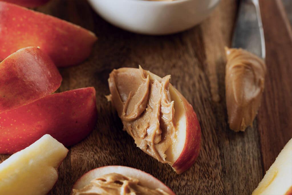 Gesunder Snack zum Abnehmen für den Heißhunger am Abend: Apfelscheiben mit Erdnussmus