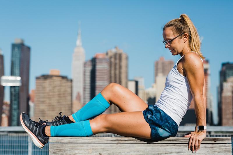 eine junge Frau in adidas-Kleidung vor der Skyline in New York