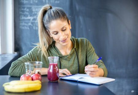 How to Build Healthy Habits: A woman writing in her journal