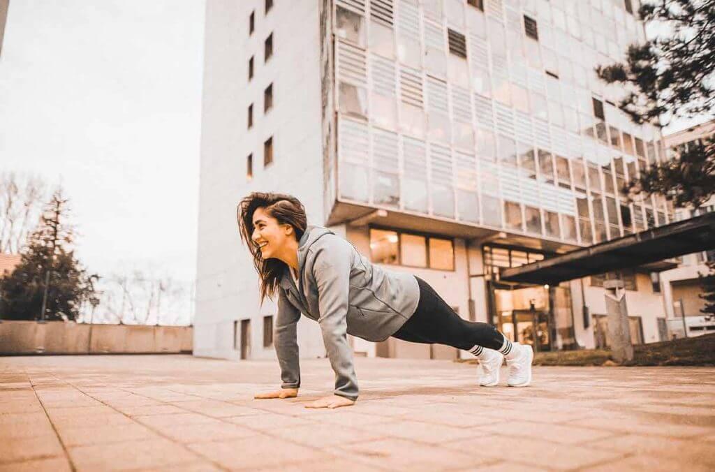 mujer en plancha al aire libre para estar en forma