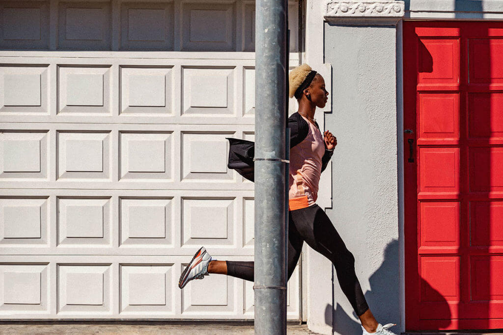 Young woman runs outside on a street to work on her running cadence
