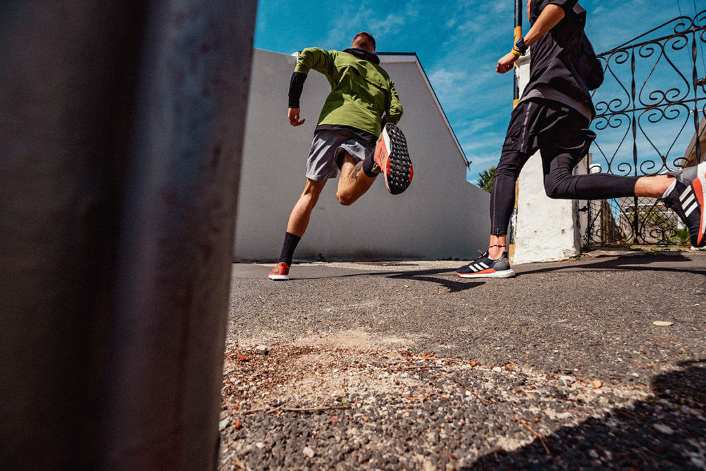 Two men running outside to improve their running cadence