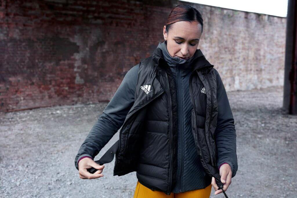 Woman in warm Adidas clothes outdoors preparing for running in winter