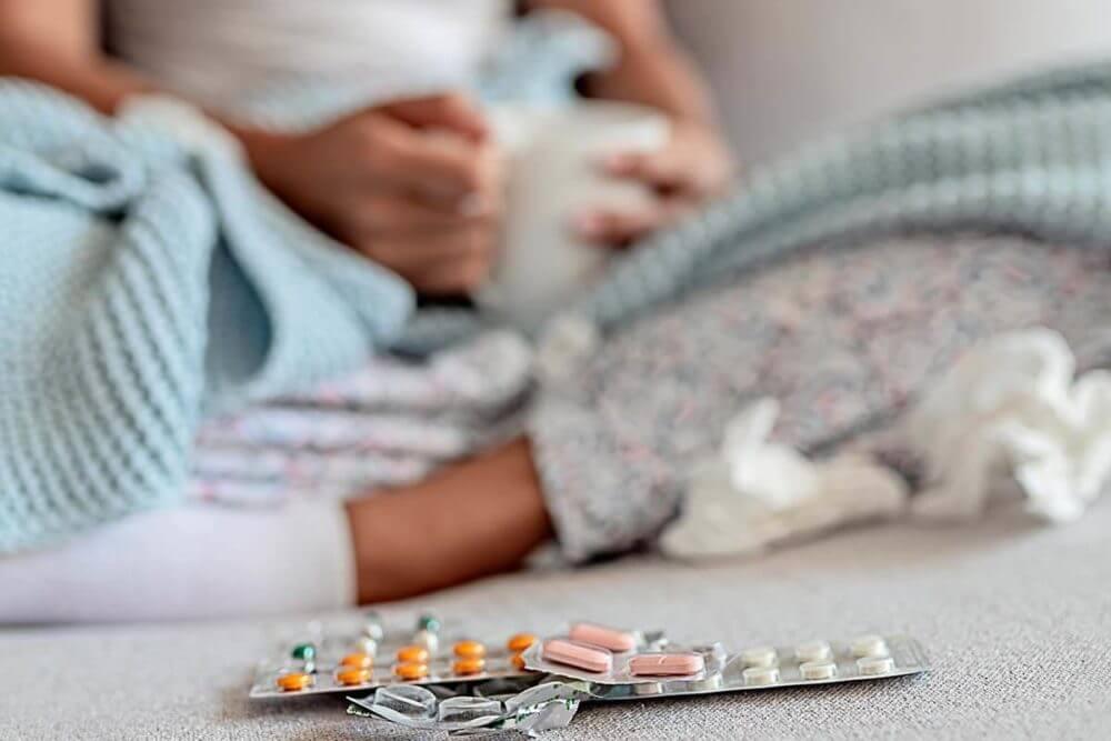 Una mujer enferma en la cama con medicamentos