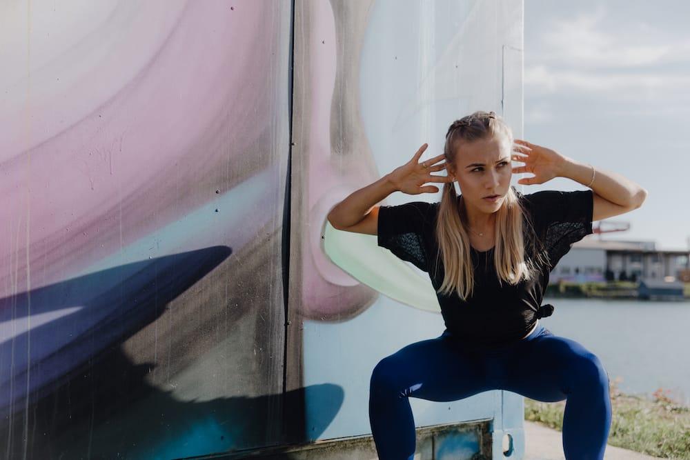 30-Day Squat Challenge: Eine junge Frau macht Kniebeugen im Freien und trägt ein Sportoutfit.