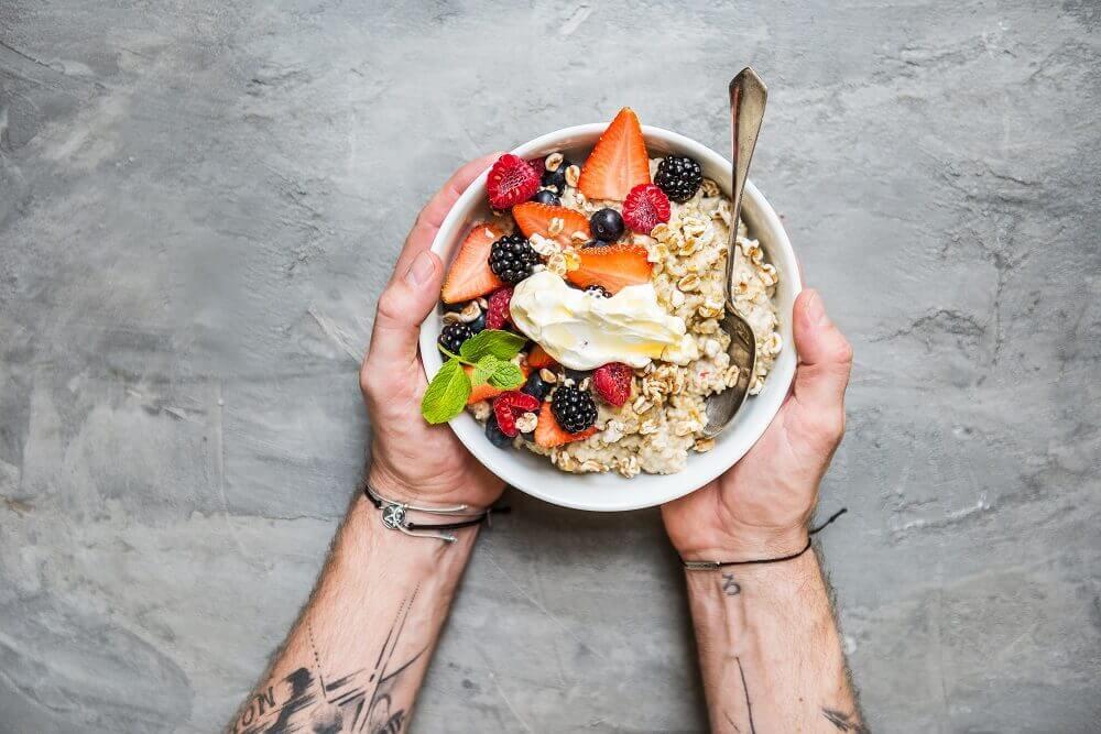 Un hombre sostiene un tazón de cereal y fruta en sus manos