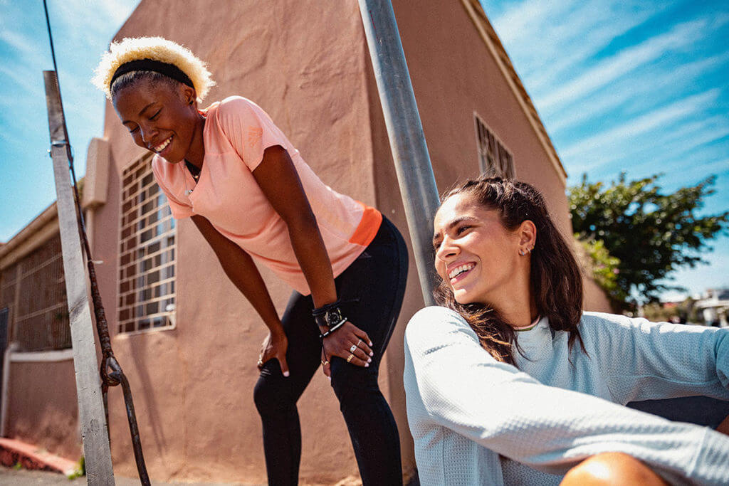 Two women wearing training clothes and are smiling