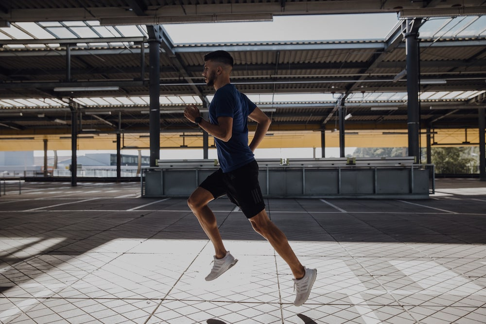 A young man who has done upper body exercises is running outdoors