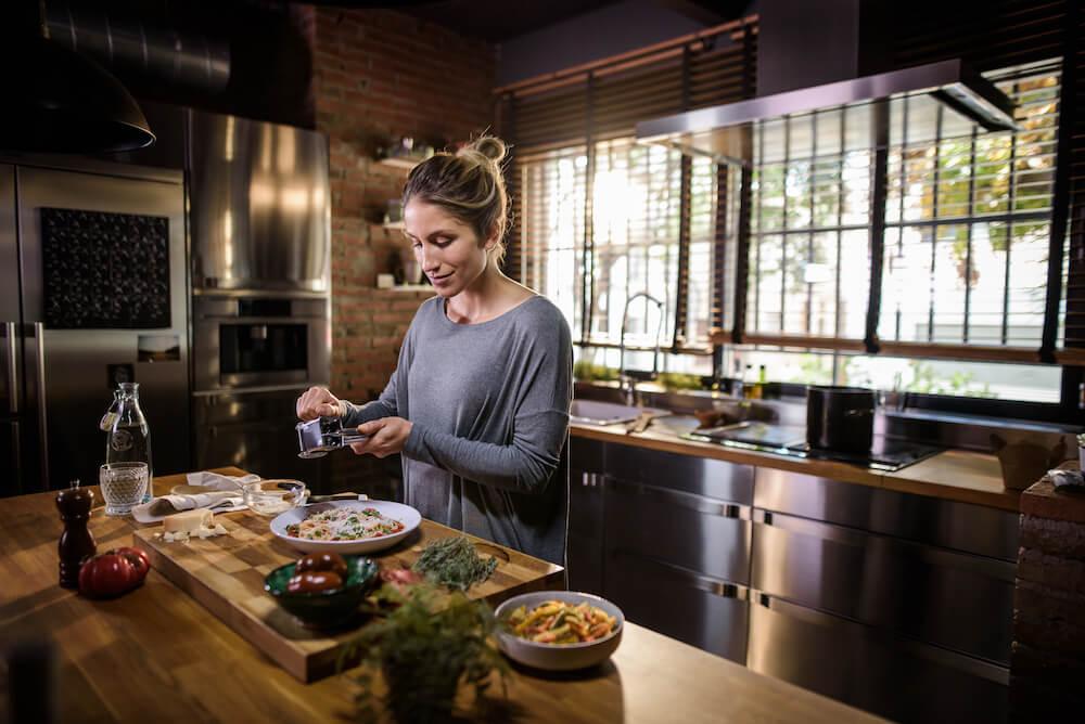 Mulher em uma cozinha preparando uma refeição saudável durante a janela de alimentação