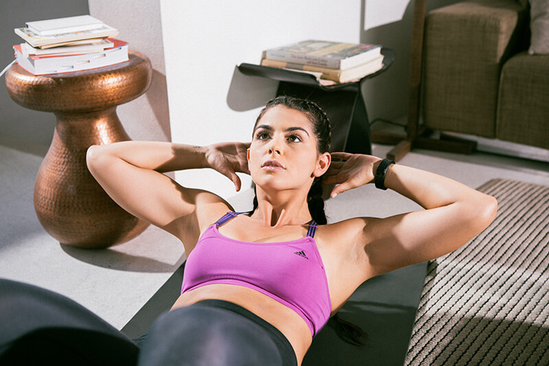 Young woman doing sit ups at home.