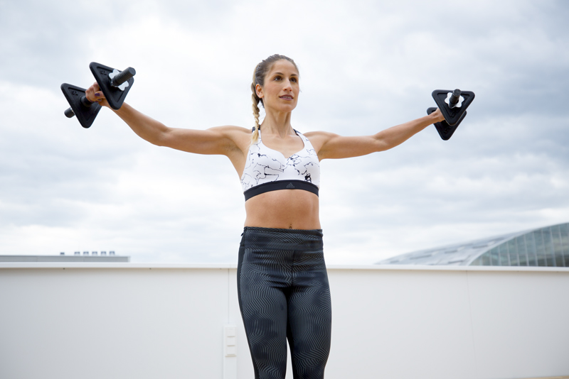 Young woman is doing front-to-side raises