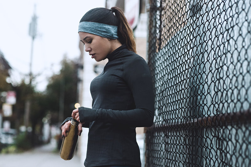 Young women in sports clothes is holding a water bottle in her hand