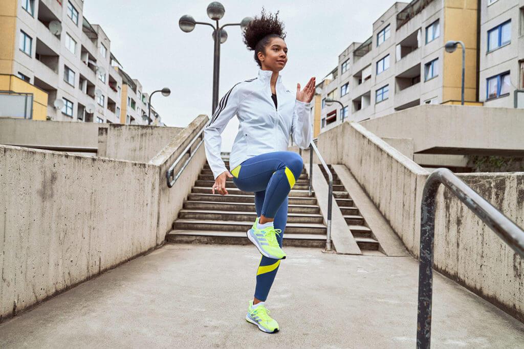 Eine Frau absolviert Aufwärmungen auf der Straße um sich auf einen Halbmarathon vorzubereiten
