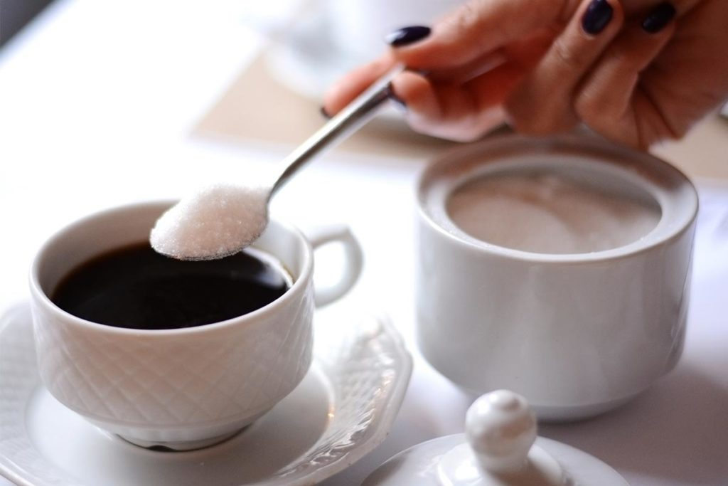 Jemand gibt einen Löffel Zucker in schwarzen Kaffee