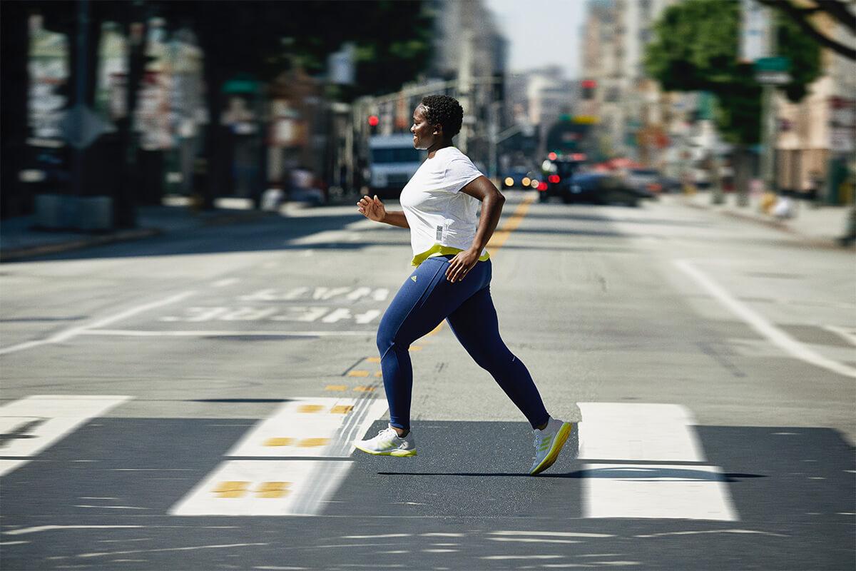 Mujer corriendo por la ciudad con calzado de adidas