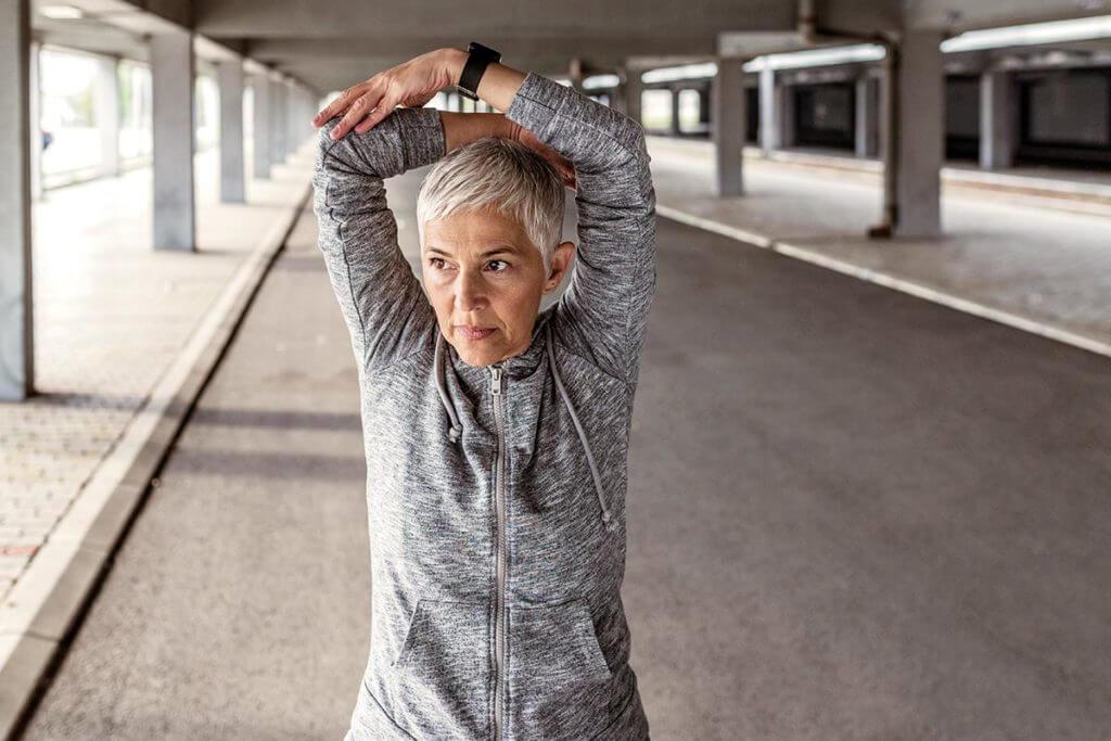 una donna di mezza età fa stretching prima di correre