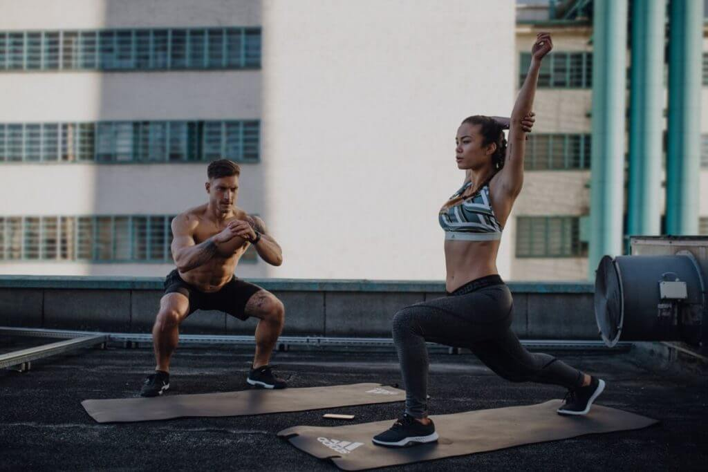 uomo e donna stretching su un rooftop