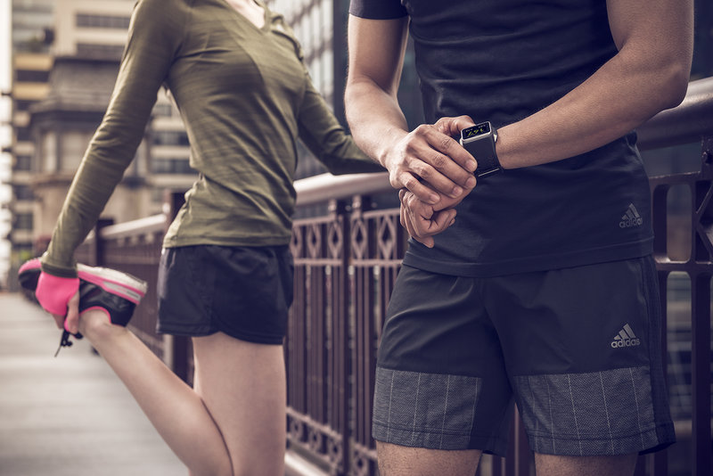 A man is checking is watch after his run, a woman is stretching