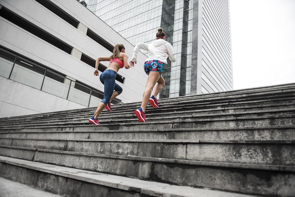 deux personnes courent dans des escaliers