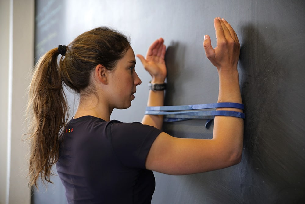 Woman doing shoulder exercise with a resistance band