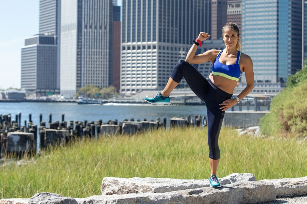 Woman doing Standing Knee-to-elbow exercise